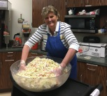 Fritzi gets to the bottom of the coleslaw to get that dressing all mixed in.